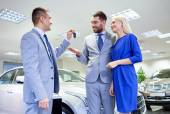 Happy couple with car dealer in auto show or salon — Stockfoto
