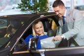 Happy woman with car dealer in auto show or salon — Stock Photo