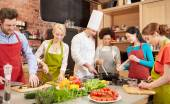 Happy friends and chef cook cooking in kitchen — Stockfoto