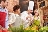 Happy friends en chef kok koken in de keuken — Stockfoto