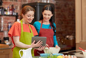 Happy women with tablet pc cooking in kitchen — Stockfoto
