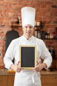Happy male chef with blank menu board in kitchen — Stock Photo