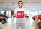Happy man with sale sigh over auto show background — Stock Photo