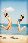 Girls jumping on  beach — Stock Photo