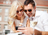 Couple looking at smartphone in cafe — Stock Photo