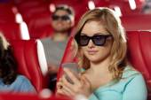 Woman with smartphone in 3d movie theater — Stock Photo