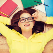 Student in eyeglasses lying on floor — Stock Photo