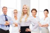 Smiling businesswoman over office team — Stock Photo
