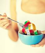 Woman  holding bowl with measuring tape — Stock Photo