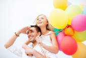 Couple with colorful balloons at seaside — Stock Photo