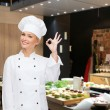 Smiling female chef showing ok hand sign — Stock Photo #67230707
