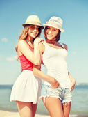 Girls in hats on the beach — Stock Photo