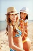 Girls in bikinis with ice cream on the beach — Stock Photo