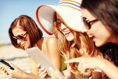 Girls with tablet pc on the beach — Stockfoto