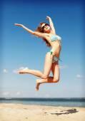 Woman in bikini jumping on the beach — Stock Photo