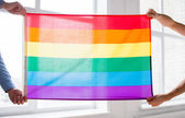 Close up of male gay couple holding rainbow flag — Stock fotografie