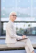 Joven empresaria sonriente con aire libre de bloc de notas — Foto de Stock