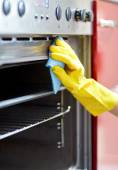 Close up of woman cleaning oven at home kitchen — Stock Photo