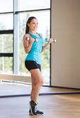 Smiling woman exercising with dumbbells in gym — Stock Photo