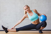 Mujer sonriente con bola del ejercicio en el gimnasio — Foto de Stock