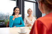 Happy young women drinking tea or coffee at cafe — Stock Photo