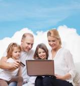 Happy family with laptop computer and credit card — Stock Photo