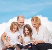 Šťastná rodina s knihou doma — Stock fotografie