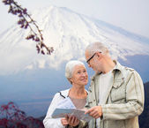Happy senior couple with travel map over mountains — Stock Photo