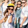 Teenage girl with headphones and friends outside — Stock Photo #67631265