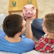Close up of couple with piggy bank sitting on sofa — Stock Photo #67631991