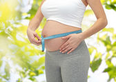 Close up of pregnant woman measuring her tummy — Stock Photo