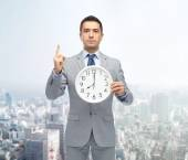 Businessman in suit holding clock with 8 oclock — Stock Photo