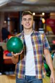 Happy young man holding ball in bowling club — Stock Photo