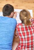 Close up of couple with  blueprint at home — Stock Photo