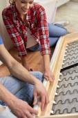 Close up of couple assembling furniture at home — Stock Photo