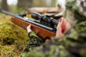 Soldier or hunter shooting with gun in forest — Stock Photo