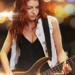 Red haired woman playing guitar on stage — Stock Photo #67964545