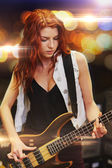 Red haired woman playing guitar on stage — Stockfoto