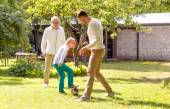 Happy family playing football outdoors — Stockfoto