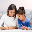 Happy mother and daughter drawing with pencils — Stock Photo #67992787