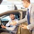 Happy man with car dealer in auto show or salon — Stock Photo #67994941