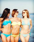 Meisjes in bikini's wandelen op het strand — Stockfoto