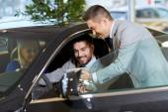 Glückliches Paar mit Autohändler im Auto-Show oder salon — Stockfoto
