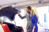 Happy couple with car dealer in auto show or salon — Stok fotoğraf