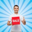 Smiling man with red sale sigh showing thumbs up — Stock Photo #68382465
