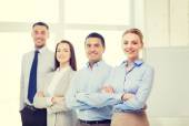 Smiling businesswoman in office with team on back — Stockfoto
