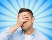 Unhappy man covering his eyes by hand — Stock Photo