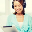Smiling woman with tablet pc and headphones — Stock Photo #68453247