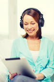 Smiling woman with tablet pc and headphones — Stock Photo