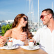 Smiling couple eating dessert at cafe — Stock Photo #68488591